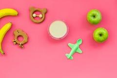Owocowy puree dla dziecka Zgrzyta z jedzeniem, jabłko, banan, zabawki na różowej tło odgórnego widoku kopii przestrzeni Zdjęcie Royalty Free