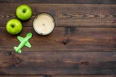 Owocowy puree dla dziecka Zgrzyta z jedzeniem, jabłko, zabawki na ciemnej drewnianej tło odgórnego widoku kopii przestrzeni Zdjęcia Stock