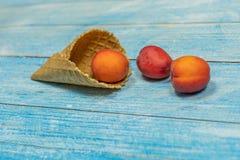 owocowy sezon Owocowy lody Morela w gofrze na błękitnym drewnianym tle obraz royalty free