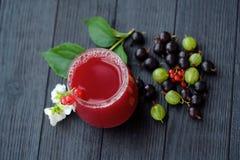 Owocowy sok i jagody na drewnianym tle Obrazy Stock