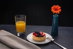 Owocowy tarta na łupkowym stole z szkłem sok pomarańczowy i kwiat w wazie obrazy stock