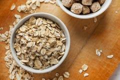 Owsów płatki i pszeniczny otręby w ceramicznych pucharach na drewnianym stole, odgórny widok zdjęcie royalty free