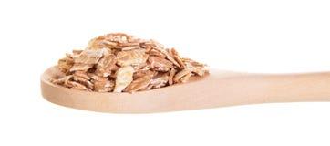 Owsów płatki w drewnianej łyżce odizolowywającej na bielu Obrazy Royalty Free