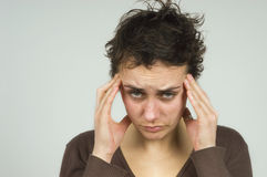 Oww, headache... Portrait of a pretty brunette suffering from headache or stress Stock Photos