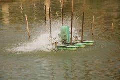 Oxígeno del terraplén de la rueda de turbina del aerador en el agua en el lago Imagen de archivo libre de regalías