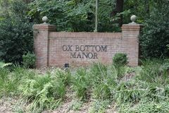 Ox Bottom Manor Neighborhood Sign on a Brick Wall in the Day. Tallahassee, FL, USA - July 14, 2018: Ox Bottom Manor neighborhood wall sign with two pillars near stock image