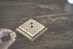 Ox tic-tac-toe game made by wood block on wooden table. educatio. Ox tic tac toe game made by wood block on wooden table. risk, strategy, competiton in business Stock Photo
