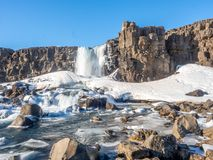 Oxararfoss waterfall in winter of Iceland. Oxararfoss, the strong waterfall in Thingvellir national park, in winter season with ice and snow in water, surrounded Stock Image