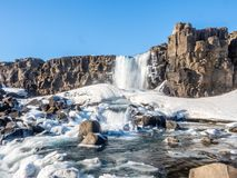 Oxararfoss waterfall in winter of Iceland. Oxararfoss, the strong waterfall in Thingvellir national park, in winter season with ice and snow in water, surrounded Royalty Free Stock Images