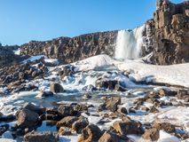 Oxararfoss waterfall in winter of Iceland. Oxararfoss, the strong waterfall in Thingvellir national park, in winter season with ice and snow in water, surrounded Stock Photos