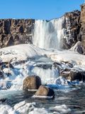 Oxararfoss waterfall in winter of Iceland. Oxararfoss, the strong waterfall in Thingvellir national park, in winter season with ice and snow in water, surrounded Stock Photo