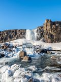 Oxararfoss waterfall in winter of Iceland. Oxararfoss, the strong waterfall in Thingvellir national park, in winter season with ice and snow in water, surrounded Royalty Free Stock Photos