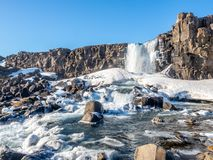 Oxararfoss waterfall in winter of Iceland. Oxararfoss, the strong waterfall in Thingvellir national park, in winter season with ice and snow in water, surrounded Stock Images