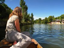 Oxford England girl on boat prow. A woman seated on a punting boat in Oxford, England looks up the river. Boating is a popular activity among Oxford University Royalty Free Stock Photos