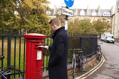 OXFORD HET UK 26 OKTOBER 2016: Mens het Posten Brief in Royal Mail-Postbox Stock Foto
