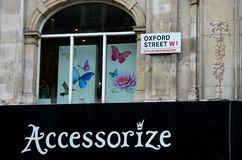 Oxford Street Accessorize shop butterflies in window London England. London, England - June 20, 2014: A black Accessorize shop sign below a window in an old Stock Photo