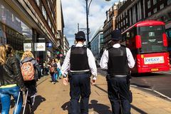 Oxford Street. Two unrecognizable police officers patrolling in the city. LONDON, UK - JUNE 9, 2015: Oxford Street. Two unrecognizable police officers in royalty free stock photo