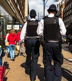 Oxford Street. Two unrecognizable police officers patrolling in the city. LONDON, UK - JUNE 9, 2015: Oxford Street. Two unrecognizable police officers in stock photos