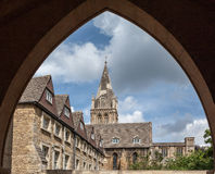 Oxford University England. Detail of the facade of a historical building with a tower framed by an ogival gothic arch in Oxford University campus, England Royalty Free Stock Photo