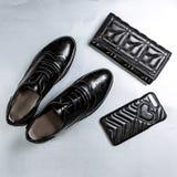 Oxfords perfor?s noirs de chaussures, une bourse et un cas de t?l?phone sur un fond blanc de papier images libres de droits
