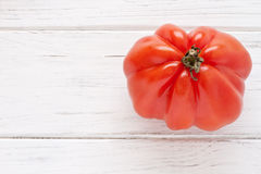 Oxheart tomato. On a white wooden board Stock Photo