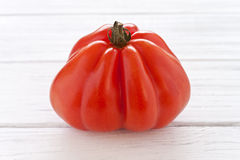 Oxheart tomato. On a white wooden board Royalty Free Stock Photography