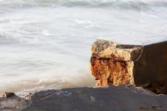 Oxidação quebrada do ferro da onda do mar da parede do cimento Foto de Stock Royalty Free