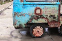 Oxidado viejo del coche con el neumático desinflado de abandonado Fotos de archivo libres de regalías