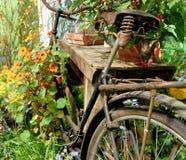 Oxidados viejos y cercado funcional ruedan no más adentro un jardín con las flores florecientes Fotografía de archivo libre de regalías
