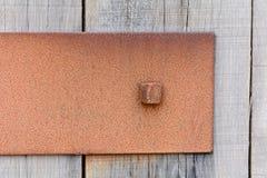 Oxiderad metallplatta som fästas till trästaketet Arkivfoton