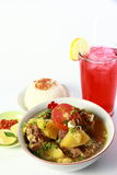 Oxtail Soup. Indonesian oxtail soup or sop buntut with potatoes and tomato in white bowl, served with white rice, chili sauce and a glass of strawberry lemonade stock images
