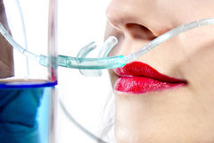 Oxygen Bar. Woman inhaling flavored oxygen with cannula and scented water royalty free stock image