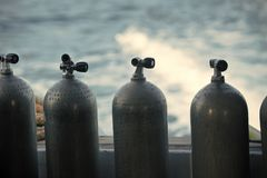 Oxygen compressed air in black steel bottles. With regulators for scuba diving extreme sport on blue water background stock image