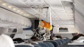 Oxygen Mask falling out in Airplane. Yellow and White Royalty Free Stock Photo