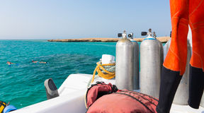 Oxygen tanks on the deck of the yacht near diving suit Stock Photos
