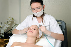 Oxygen therapy. Beautician doing oxygen therapy for young women laying down in a beauty salon royalty free stock image