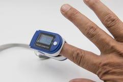 Oxymètre d'impulsion dans un bout du doigt patient masculin du ` s sur le fond blanc photo libre de droits