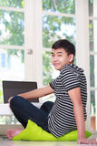 Oy asiático adolescente usando un ordenador portátil Foto de archivo