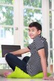 Oy asiatico adolescente facendo uso di un computer portatile Fotografia Stock
