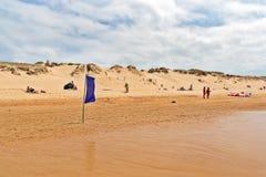 OYAMBRE SPANIEN - JULI 6, 2016: Blå flagga på den sandiga stranden i su Royaltyfria Bilder