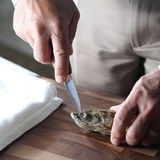 Oyster. A man is peeling an oyster shell Royalty Free Stock Photo