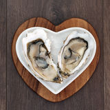 Oyster Aphrodisiac Foods on Crushed Ice. Oysters on crushed ice in a heart shaped plate on a maple wood board over old oak background stock image