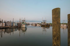 Oyster and fishing trawlers docked at sunset Stock Images
