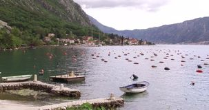 Oyster farming in Montenegro. Oyster and mussel farming with traps and buoys in Boka-Kotor bay, Montenegro, the Adriatic coast in the springtime. Mountains in stock video footage