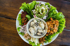 Oyster ,squid and prawn with spicy sauce and vegetables Stock Image