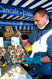 Oysterman opening oysters at market of Cancale. France, editorial Royalty Free Stock Photos