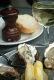 Oysters. Table with a plat of oysters and the half shell with a glass of white wine Royalty Free Stock Photo