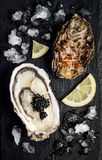Oysters with black sturgeon caviar and lemon on black slate stone background. Top view, flat lay. Stock Image