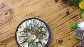 Oysters cooked with cheese and herbs on wooden copy space. Seafood composition. Italian cuisine with seafood. Food stock video footage