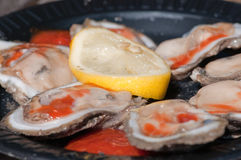 Oysters on the Half Shell. Fresh Oysters with Hot Sauce and Lemon Royalty Free Stock Images
